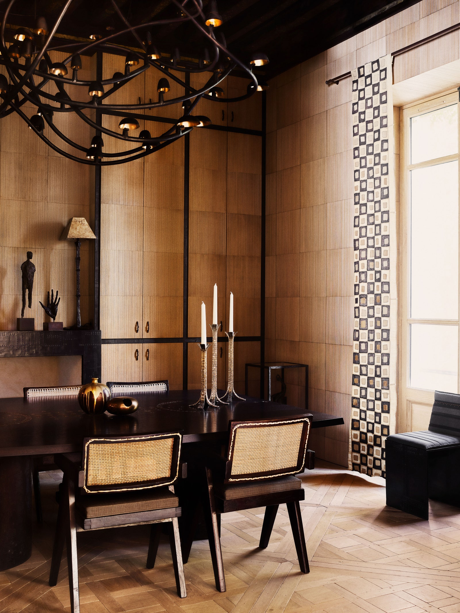 pPierre Jeanneret chairs surround the Donatdesigned dining table. Bronze chandelierbr by Frederik Molenschot.p