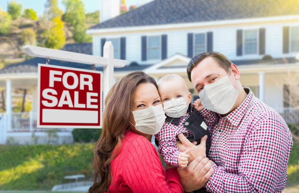 Happy Young Family Wearing Medical Face Masks In Front of New House and Sold For Sale Sign