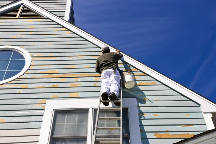 Person on ladder painting a house.