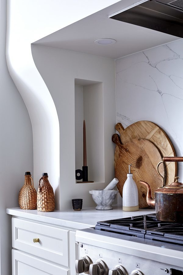Kitchen vignette with wooden pizza rounds, a mortar and pestle and a copper kettle