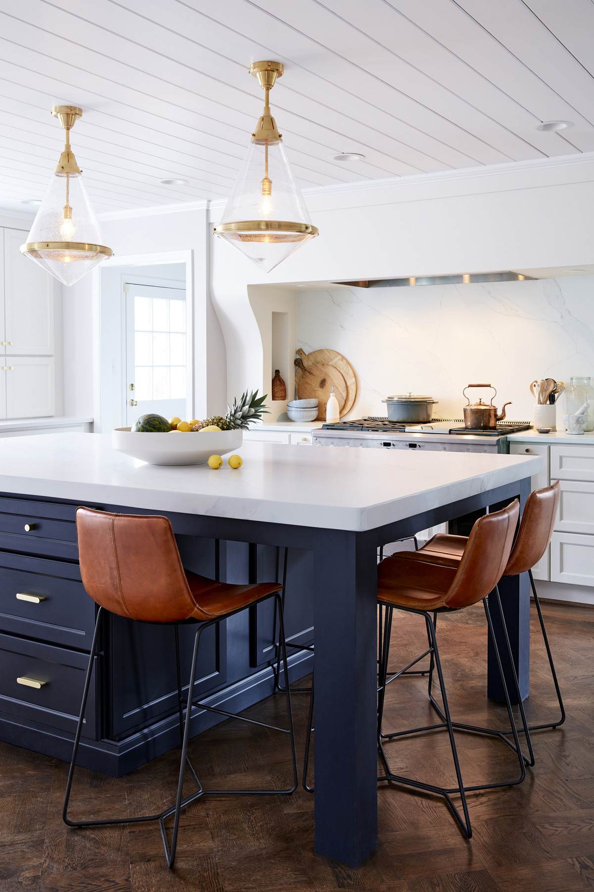 Gold and glass lighting fixtures over a dark navy kitchen island surrounded by leather stools