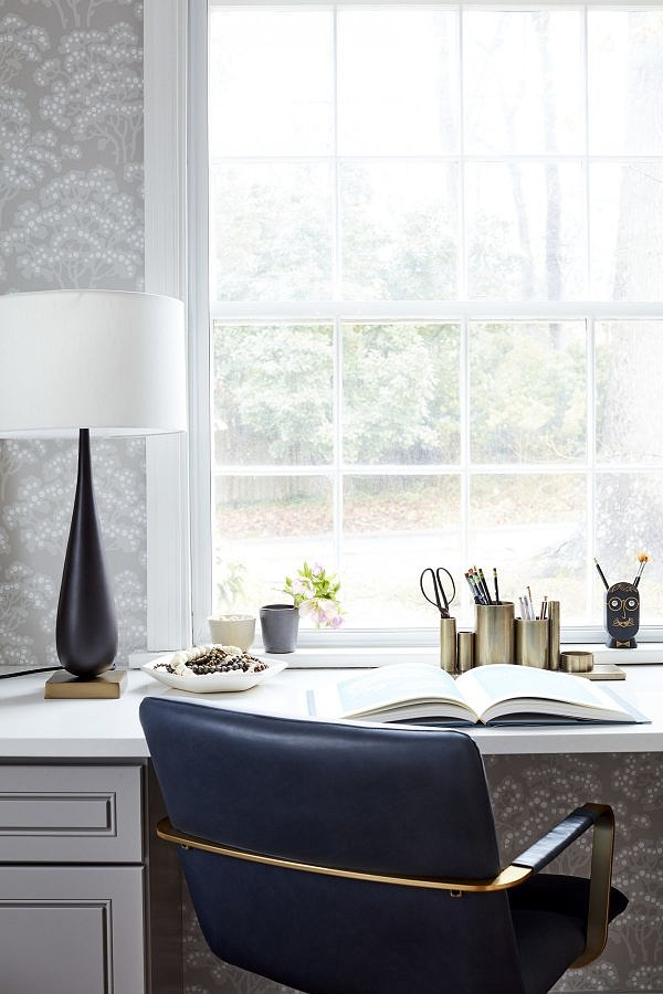 An office desk with plenty of window light and a blue and gold desk chair