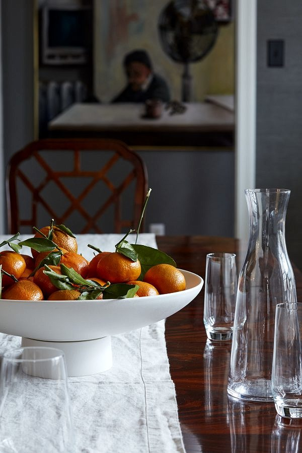 A bowl of oranges on the dining room table, with a carafe and glasses nearby