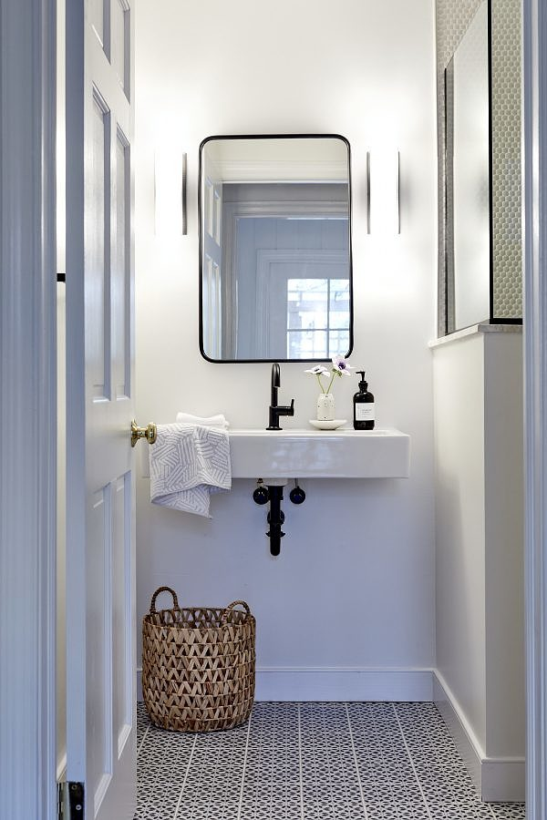 Guest bathroom with detailed floor tile and Kelly Wearstler sconces
