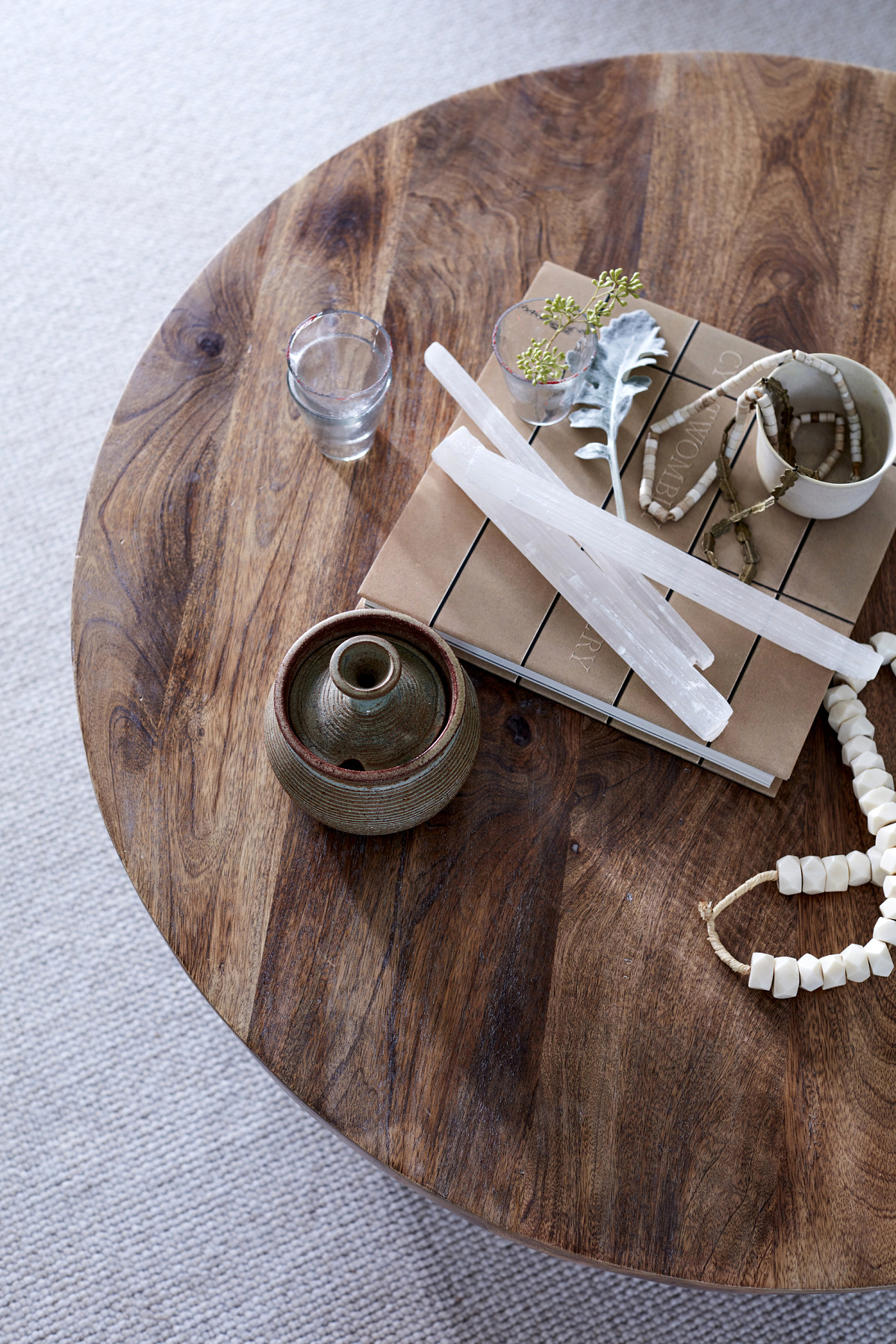 Close-up of circular wood table with African bone beads, French glass votives and other treasures